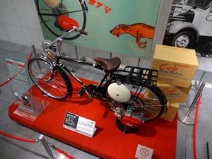 会場に展示された「ホンダ カブ F型」1952年製です。業務用自転車に補助エンジンと燃料タンクがついています。後ろに写っている箱にエンジンとタンクを詰めて出荷していました。藁のムシロで梱包するのが当たり前の時代に段ボール箱を採用したのは画期的だったそうです(「Honda原点ライブラリー」より)。