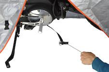 従来のバイクカバーだと、飛散防止ストラップのバックルを留める際、車体の下に潜るなど苦労したが、イージーフックを使えば車体の向こう側からヒョイとバックルを持ってこられる。原始的だがいいアイデアだ。